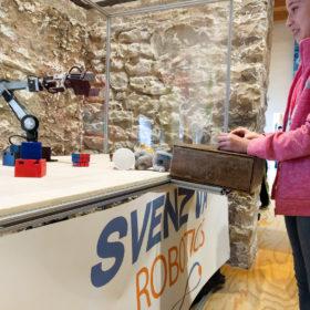 A young woman controls the Svenzva Robotics mobile robot exhibit