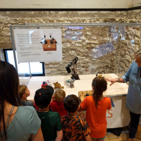 A parent instructs a child on how to control a robotic manipulator